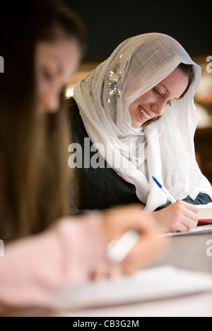 Close up of two women writing - Stock Photo