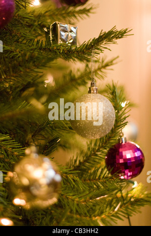 A close up view of a decorated Christmas Tree with barbels in and out of focus on as well as presents - Stock Photo