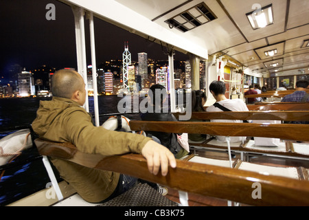 passengers on star ferry crossing victoria harbour to hong kong island at night hksar china - Stock Photo