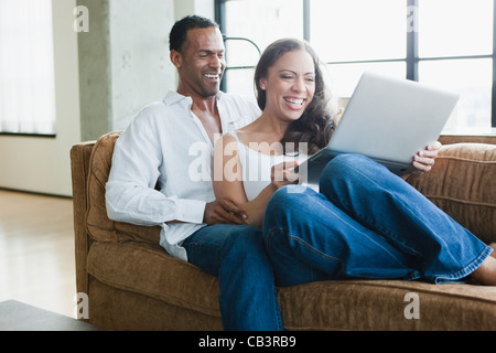 Couple sitting on couch and using laptop - Stock Photo