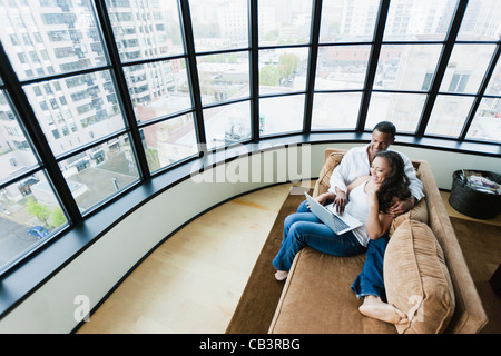 Elevated view of couple sitting on couch in loft apartment and using laptop - Stock Photo