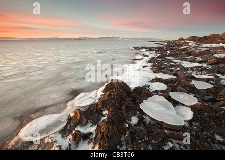 Icy coastline at sunset, at Nes on the island Jeløy, Moss kommune, Østfold fylke, Norway. - Stock Photo