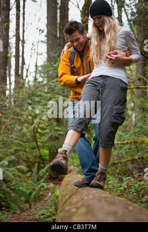 Portland, Oregon, USA, Couple walking along log in forest - Stock Photo