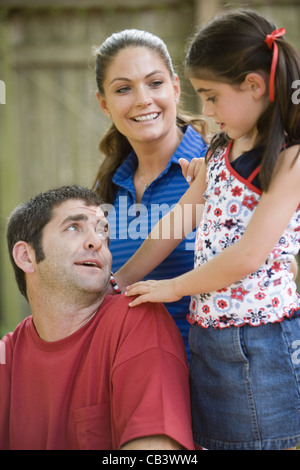 Family with young girl spending time on their backyard patio - Stock Photo