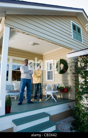 Portrait of father and son standing on porch - Stock Photo