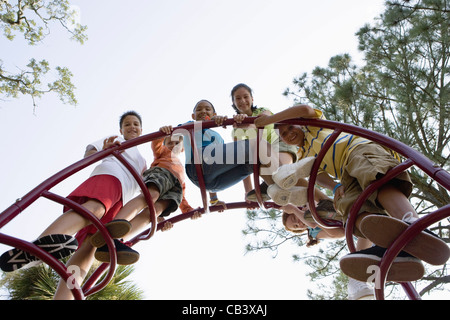 Portrait of children climbing on monkey bars at a playground - Stock Photo