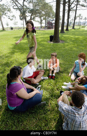 Children sitting in a circle on the grass with their teacher while a girl walks around them - Stock Photo
