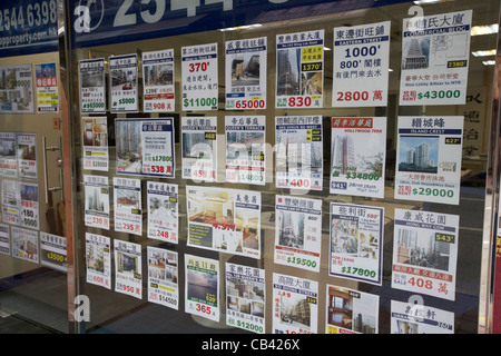 properties for sale in an estate agent window hong kong island hksar china - Stock Photo