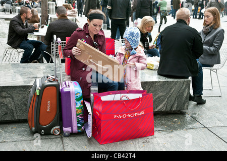 tourist mother & small daughter with Christmas shopping purchases in FAO Schwartz shopping bag on plaza outside - Stock Photo