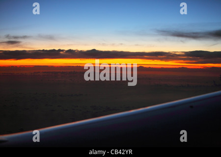 sunset above the clouds sky high shot from an flying airplane - Stock Photo