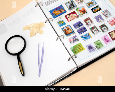 Stamp Collecting Stamp Album Tweezers Magnifying Glass Stamp Hinges and Stamps - Stock Photo