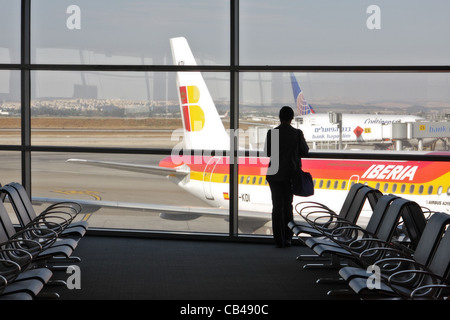 Unidentified person standing against big window in the terminal of International Airport and looking at airplanes - Stock Photo