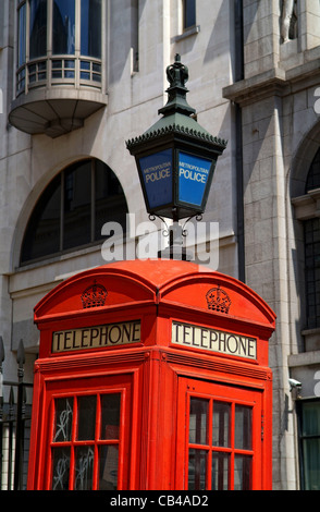 Detailed image of a red telephone box  and a metropolitan police lamp, seen close to the Strand in London - Stock Photo