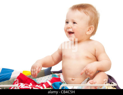 Laughing baby sitting in clothes on white background - Stock Photo