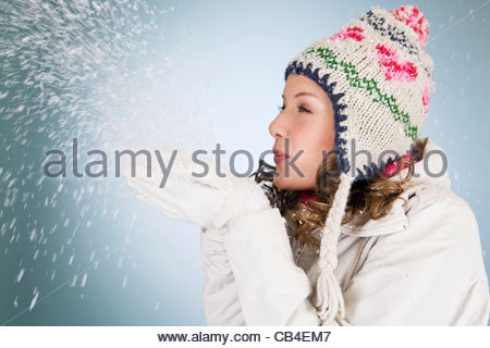 A young woman blowing a handful of snowflakes - Stock Photo