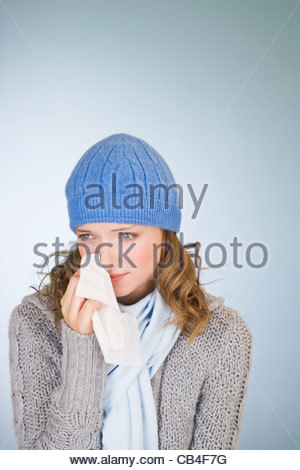 A young woman wiping her tears away with a tissue - Stock Photo