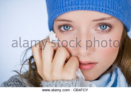 A young woman crying, wiping her tears away with a tissue, close-up - Stock Photo