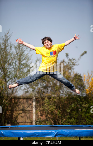 Leaping boy on trampoline - Stock Photo