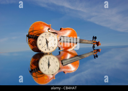 old violin and clock-face on mirror Stock Photo