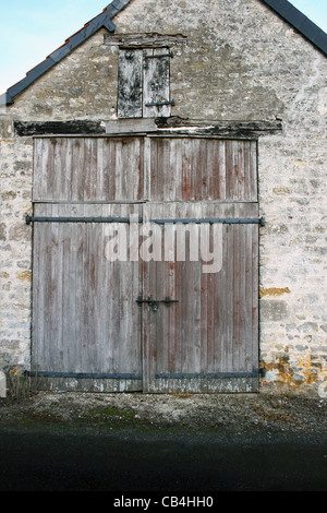 Barn like structure with old wooden doors on the end of a stone building in Fresville,France. - Stock Photo
