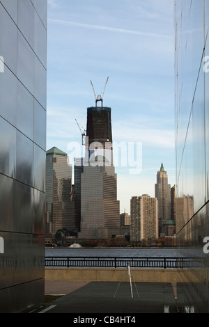 View of the Freedom Tower under construction at Ground Zero framed by the walls of the Empty Sky Memorial in Liberty - Stock Photo