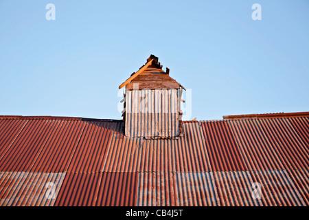 Rusty tin roof on barn in Iowa on a farm. - Stock Photo