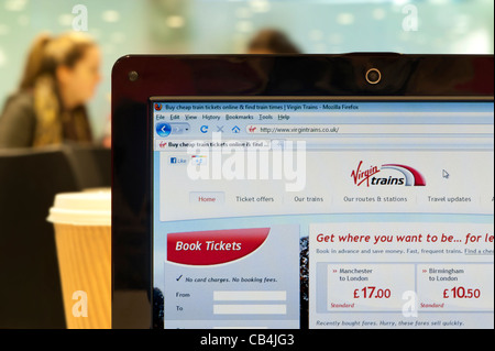 The Virgin Trains website shot in a coffee shop environment (Editorial use only: print, TV, e-book and editorial - Stock Photo