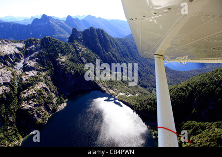 Flying over a mountain lake in Vancouver Island with a floatplane - Stock Photo