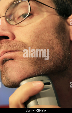 a man shaving his chin with a silver electric razor - Stock Photo