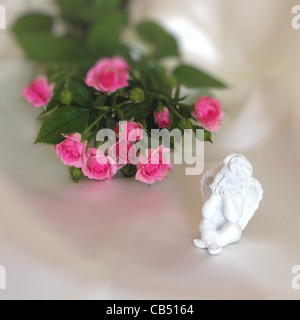 angel and rose on ivory silk - Stock Photo