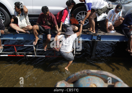 Woman moving up to truck , floodwaters at Bang Yai District , Nonthaburi , Thailand - Stock Photo