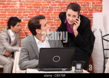 Co-workers watching laptop computer - Stock Photo