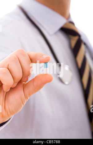 businessman holding a pill in his fingers (selective focus) - Stock Photo
