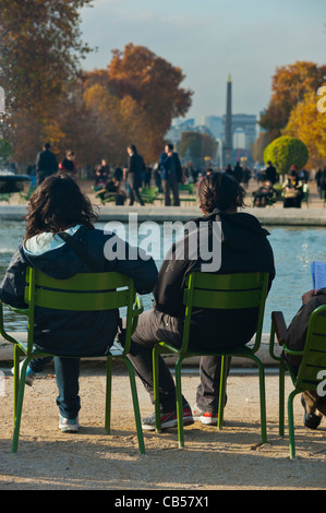 Paris, France, Young Tourist Couple, Rear, Sitting , Parks The Tuileries Garden (French: Jardin des Tuileries,) - Stock Photo