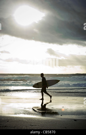 Silhouette of a surfer walking with his surfboard along the beach with stormy clouds in the background, Tarifa, - Stock Photo