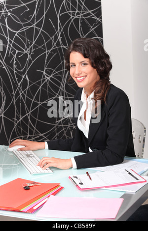 Female estate agent working at desk - Stock Photo