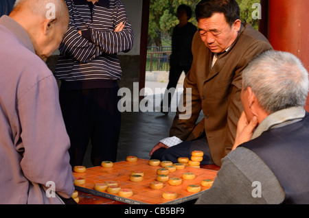 Group of men watching pair play Chinese Chess or Xiangqi in Beijing Peoples Republic of China - Stock Photo