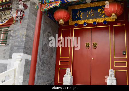 Red door with ornaments at luxury estate in Shichahai area hutong in Beijing Peoples Republic of China - Stock Photo