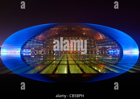 National Centre for the Performing Arts egg in blue light at night reflected in pool water Beijing Peoples Republic - Stock Photo