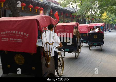 Pedicabs traffic on Qianhai Beiyan street in Shichahai area by Qianhai lake Beijing Peoples Republic of China - Stock Photo