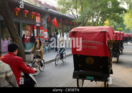 Traffic and line of pedicabs on Qianhai Beiyan street in Shichahai area at Qianhai lake Beijing Peoples Republic - Stock Photo