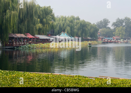 Willow trees and restaurants along Qianhai Lake in the Shichahai area of Beijing China - Stock Photo
