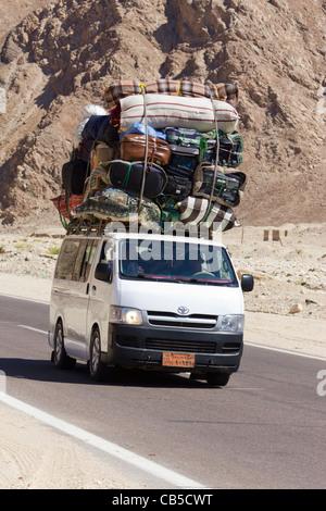 overladen minibus on the road from Nuweiba to Cairo, Sinai Peninsula, Egypt - Stock Photo
