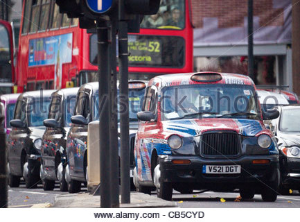 Row of black cabs waiting at traffic lights London England - Stock Photo