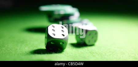 Dice and chips on green gambling baize - Stock Photo