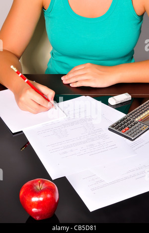Student doing maths exercises with a calculator and a red pencil. - Stock Photo
