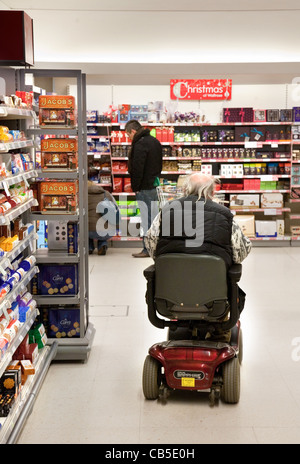disabled man shopping on his disability scooter in a Waitrose supermarket, UK - Stock Photo