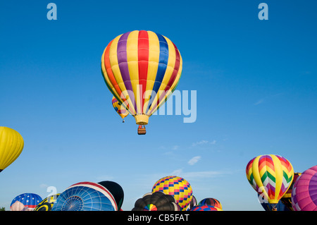 Hot-air balloons ascending over inflating ones on the ground - Stock Photo