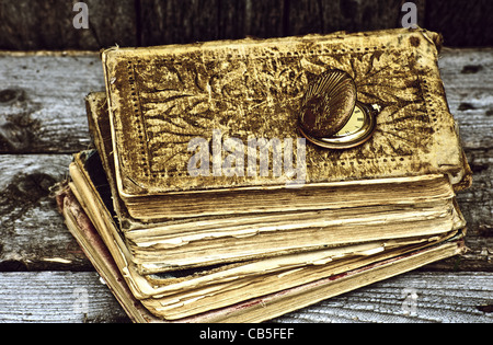 High contrast conceptual image with a pile of antique books with an old pocket watch on a grunge background - Stock Photo