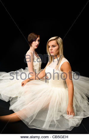 two teen girl ballet dancers sitting in a tutu on a white background - Stock Photo